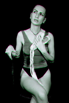 Black and white photo showing ju90, dressed in a silver vest and black g-string, sitting and looking into the distance, with a pair of ballet shoes in her left  hand and her right hand resting on her walking stick.