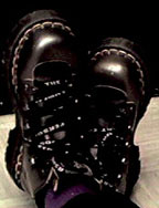 Photograph of a woman's feet in silver and black boots, crossed at the ankles as she lies on the floor.