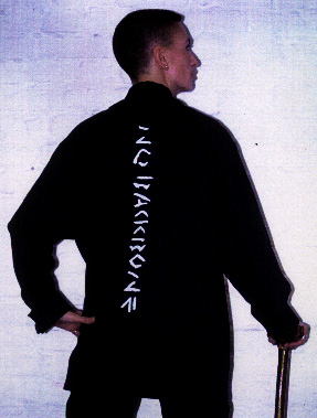 "Photograph of Ju standing with her walking stick with her back to the viewer, wearing a black shirt with the words ""No Backbone"" printed down her spine"