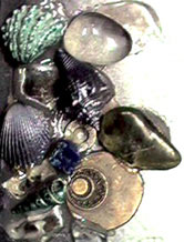 Close-up photograph of crystals, shells etc on the front of Ju's brace