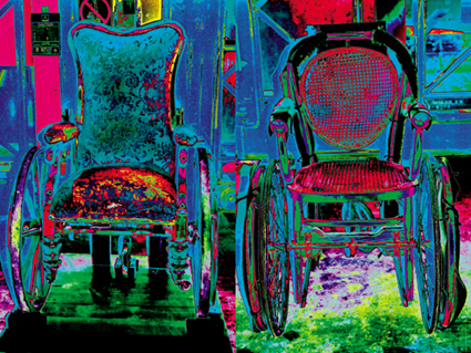 This is a colour photograph of old-fashioned wheelchairs in the Science Museum stores, digitally manipulated so that they glow with bright colours.