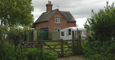 Colour photograph of a white caravan from outside the wooden orchard gates, framed by trees, with a red brick tiled cottage behind it. If you look very carefully, you can see a Westie immediately behind the gate.