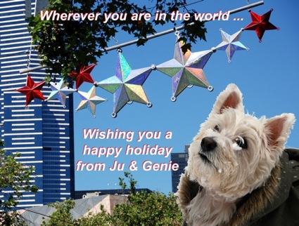 Colour photograph of a Westie in the snow set in front of xmas decorations in the street in the sunshine, bearing the text Wherever you are in the world...Wishing you a happy holiday from Ju & Genie
